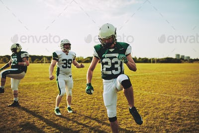 Football players doing warm ups together on a sports field