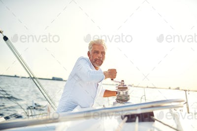 Mature man standing on his boat winding a winch