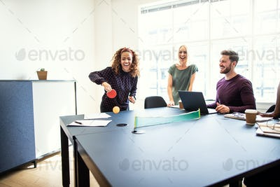 Laughing coworkers playing table tennis during their work break