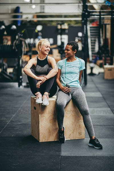 Fit young women laughing together after a gym workout