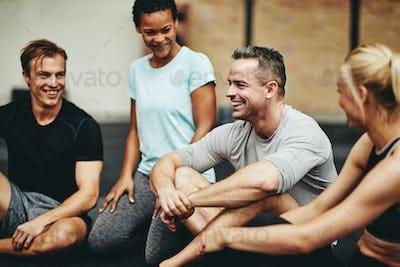 Diverse friends laughing on a gym floor after working out