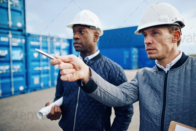 Engineers tracking shipping inventory in a freight container yard