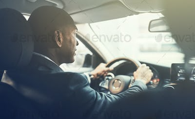 Young African businessman commuting to work in his car