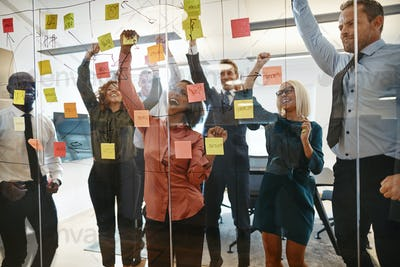 Cheering businesspeople celebrating during an office brainstorming session