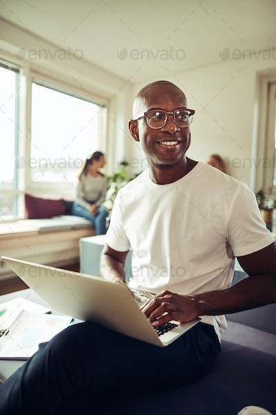 Smiling African businessman using a laptop at his office desk
