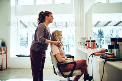 Smiling hairdresser finishing a female client's haircut in her salon