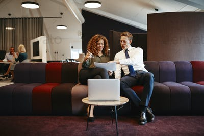 Smiling businesspeople sitting on an office sofa discussing work