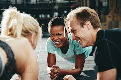 Smiling group of friends planking together on a gym floor