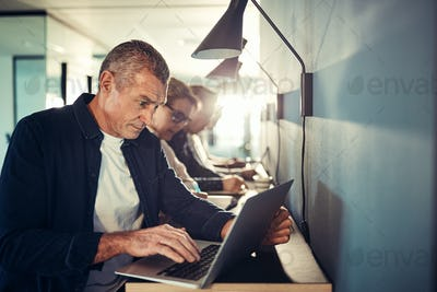 Mature male designer working online with colleagues in the background