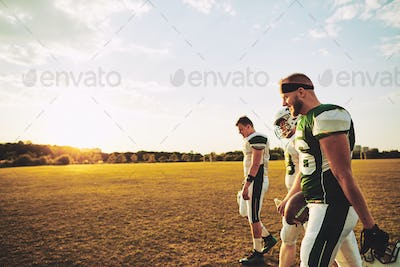 Team of American football players walking off a sports field
