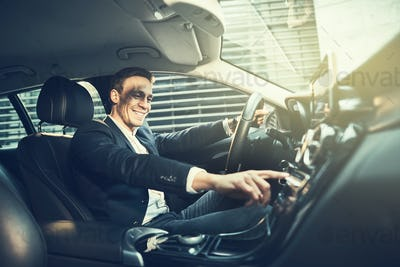 Smiling businessman enjoying a drive through the city