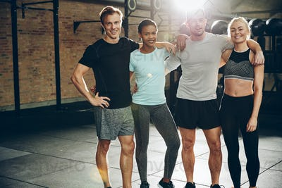 Smiling friends in a gym after working out together