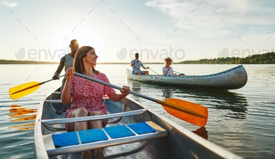 Young woman smiling while canoeing with friends in the summer