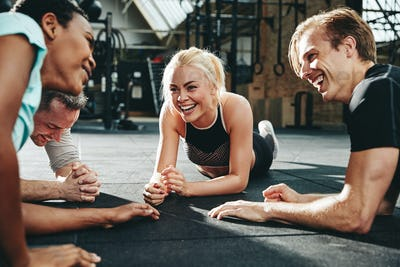 Laughing people lying on a gym floor after working out