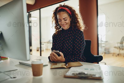 Young businesswoman sitting at her desk reading a text message