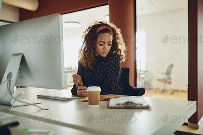 Young businesswoman sitting at her workstation in an office