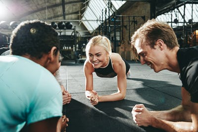 Gym friends smiling and planking together during a workout class