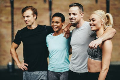Smiling group of diverse friends standing together in a gym