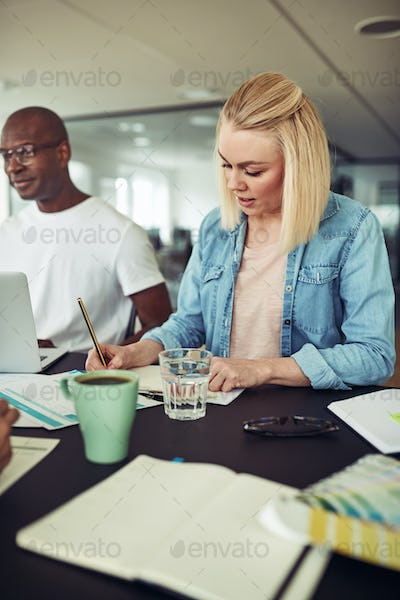 Focused businesswoman working with a colleague at an office table