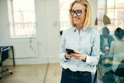 Laughing young businesswoman reading a text message in an office