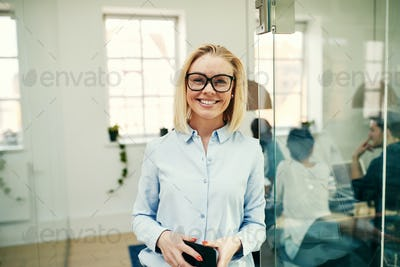 Smiling businesswoman holding her cellphone  in a bright modern office