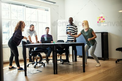 Young designers playing table tennis together inside of an office