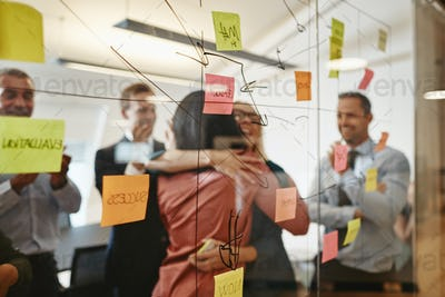 Two businesswomen hugging during an office brainstorming session