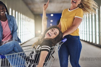 Girlfriends pushing their friend in a shopping cart at night