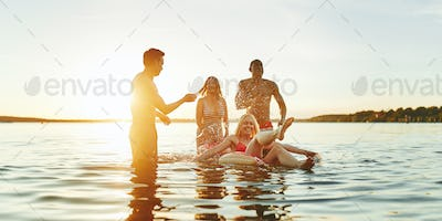 Laughing friends splashing each other in a lake at sunset