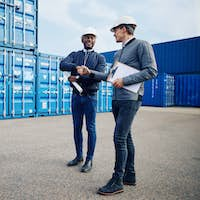 Smiling engineers shaking hands together in a shipping yard