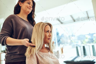 Young woman talking with her hairstylist in a salon