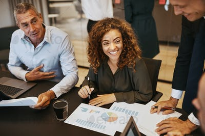 Smiling young businesswoman discussing graphs with office colleagues