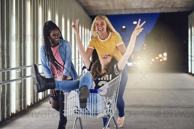 Carefree female friends playing with a shopping cart at night