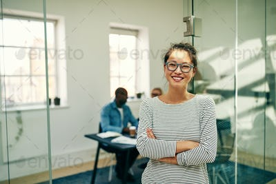 Laughing young Asian businesswoman standing in a modern office