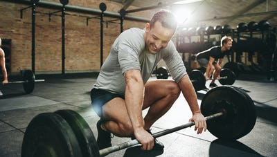 Man smiling while preparing to lift weights at the gym