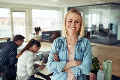Young businesswoman smiling with coworkers sitting in the background