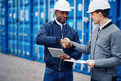 Engineers standing in a shipping yard shaking hands together