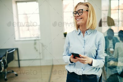 Laughing young businesswoman standing with her cellphone at work