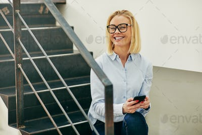 Laughing young businesswoman sitting on office stairs reading text messages