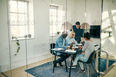 Diverse young businesspeople discussing work together in an office boardroom
