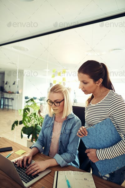 Two businesswomen working together in an office using a laptop