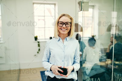 Smiling young businesswoman holding her cellphone in an office