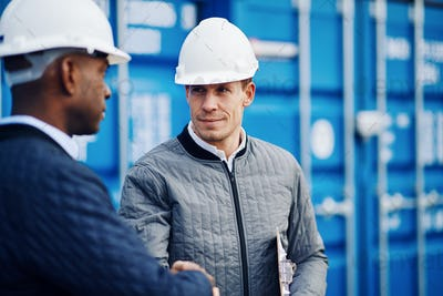 Two engineers shaking hands together in a shipping yard