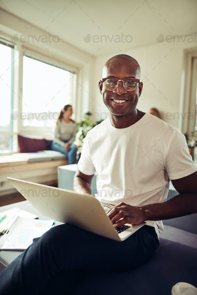 Smiling African businessman working on a laptop at his desk