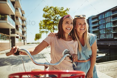 Two laughing girlfriends walking with a bicycle through the city