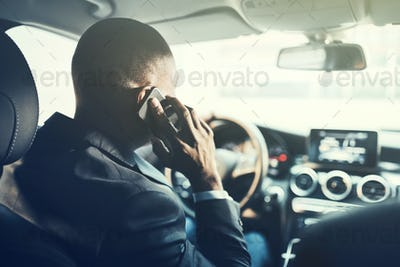 African businessman driving in the city talking on his cellphone