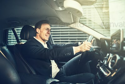 Young businessman smiling while driving through the city