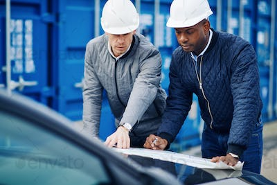 Two engineers standing in a commercial shipping yard discussing blueprints