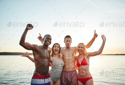 Carefree friends having fun together in a lake at sunset