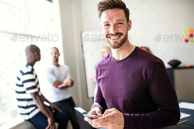 Smiling young designer using his cellphone in an office